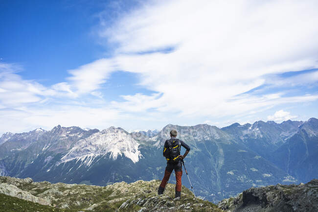Hiker standing on top of peak while looking at mountains, Western Rhaetian Alps, Sondrio, Italy — Stock Photo