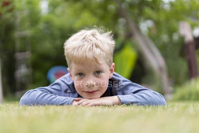 Милый блондин лежит на траве на заднем дворе. — стоковое фото