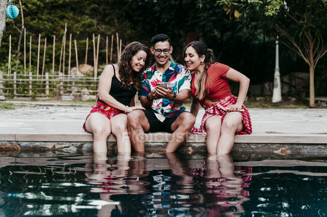 Man showing phone while sitting by women at poolside — Stock Photo
