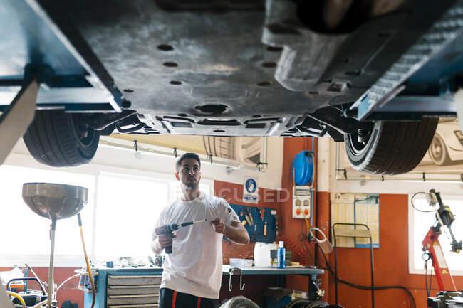 Jovem mecânico segurando ferramenta de trabalho olhando para o carro enquanto em pé na oficina de reparação de automóveis — Fotografia de Stock