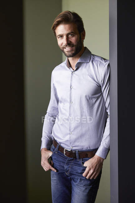 Man with hands in pockets standing against green wall in office — Stock Photo