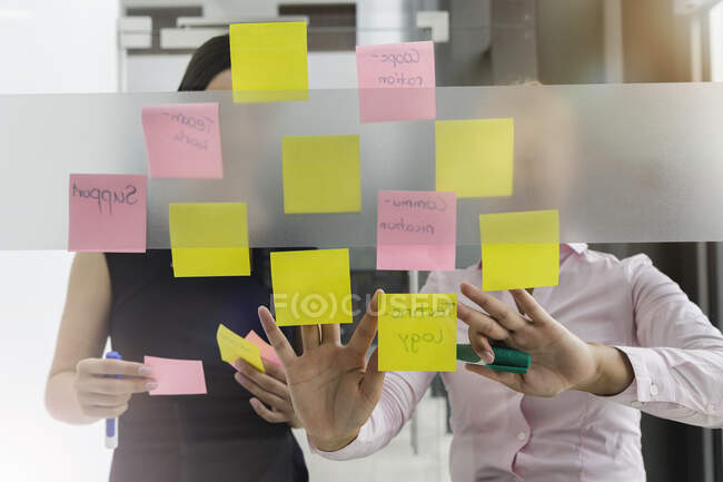 Female professionals discussing over adhesive notes stuck on glass wall in office — Stock Photo