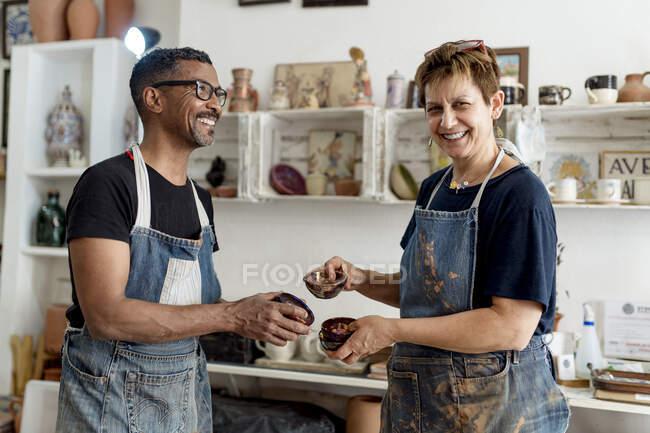 Художні художники тримають кераміку, стоячи в майстерні. — стокове фото