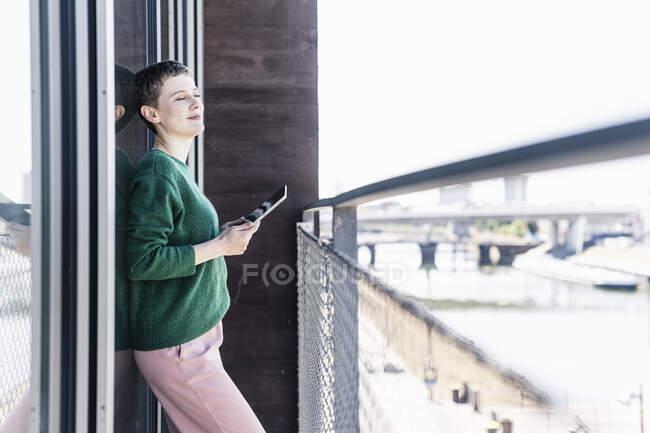 Деловая женщина с закрытыми глазами держит цифровой планшет, стоя на балконе — стоковое фото