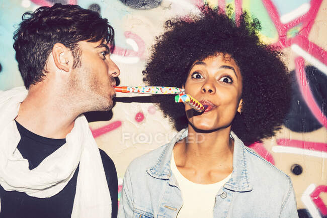 Close-up of carefree couple blowing party horns against wall at night — Stock Photo