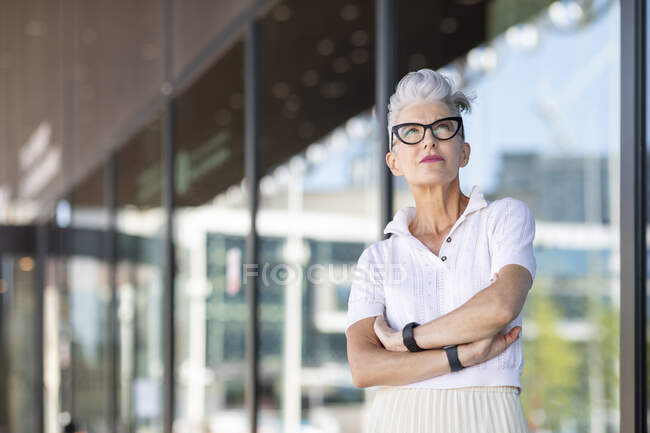 Contemplating senior female with arms crossed standing against glass window — Foto stock