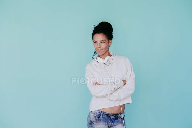 Beautiful woman with arms crossed looking away while standing against turquoise background — Stock Photo
