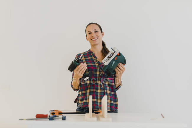 Smiling woman holding electric jigsaw and drill while standing against white wall at home — Stock Photo