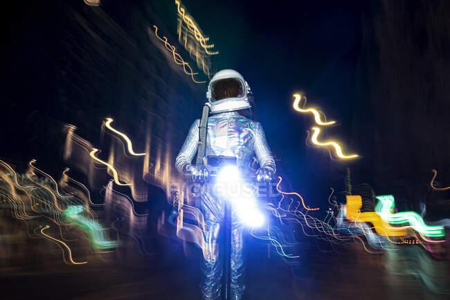 Чоловічий астронавт у космічному костюмі стоїть серед світлих картин на вулиці вночі. — стокове фото