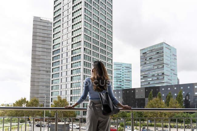 Vista posteriore della donna con borsa in piedi contro ringhiera in città durante COVID-19 — Foto stock