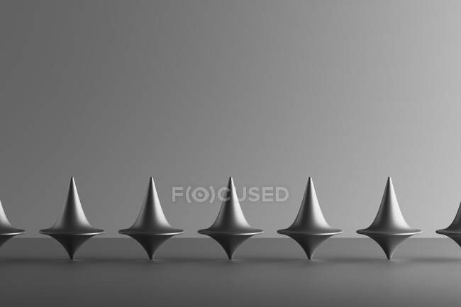 Three dimensional render of row of metallic spinning tops — Stock Photo