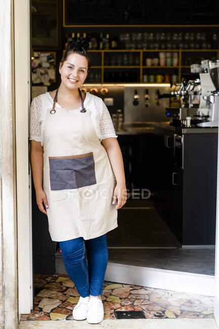 Улыбающаяся хозяйка, стоящая у стеклянной двери у входа в кофейню — стоковое фото