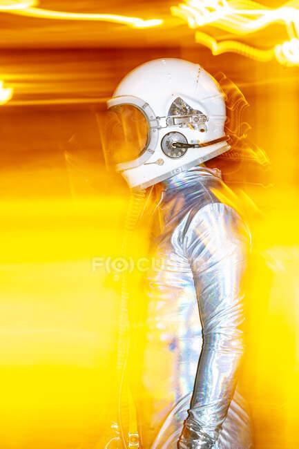 Hombre adulto medio usando traje espacial de pie en medio de la luz abstracta - foto de stock