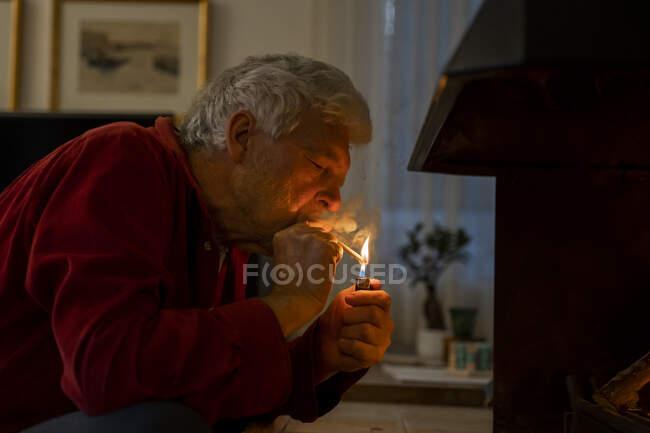 Hombre mayor encendiendo el cigarrillo con encendedor mientras está sentado en casa - foto de stock
