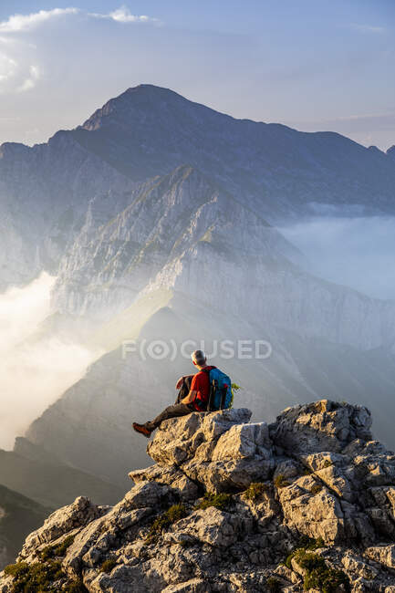 Man sitting on top of mountain peak at Bergamasque Alps, Italy — Stock Photo
