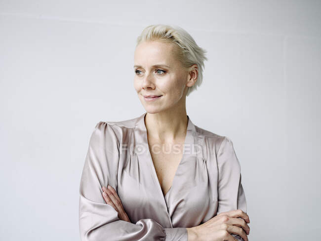 Thoughtful businesswoman with arms crossed standing against white wall in office — Stock Photo