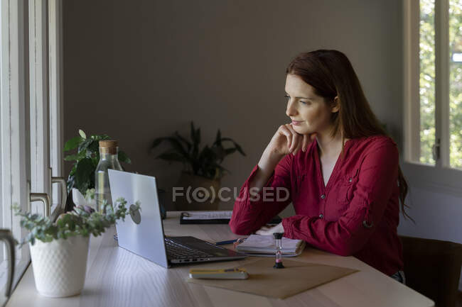 Psychologist with head in hands listening to video call on laptop while sitting at home — Stock Photo