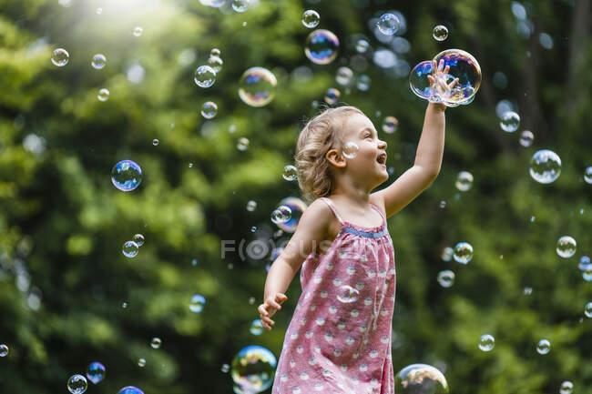 Весела дівчина серед бульбашок у парку. — стокове фото