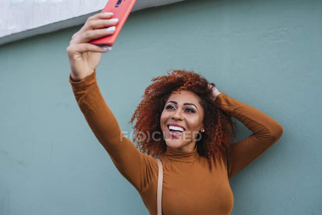 Fröhliche junge Afro-Frau macht Selfie mit Smartphone, während sie an der Wand steht — Stockfoto
