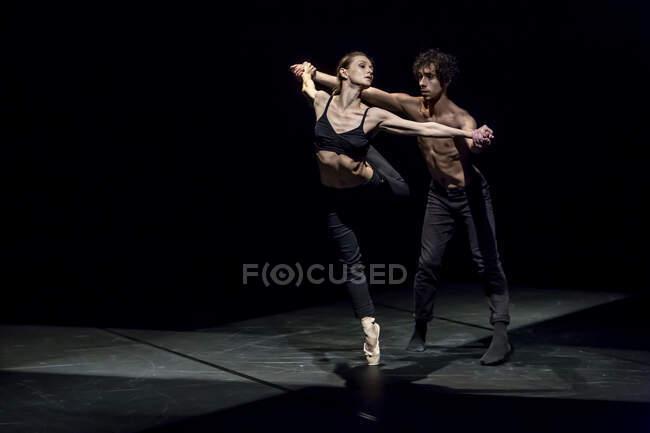 Мужчина и женщина танцуют современный балет на черной сцене — стоковое фото