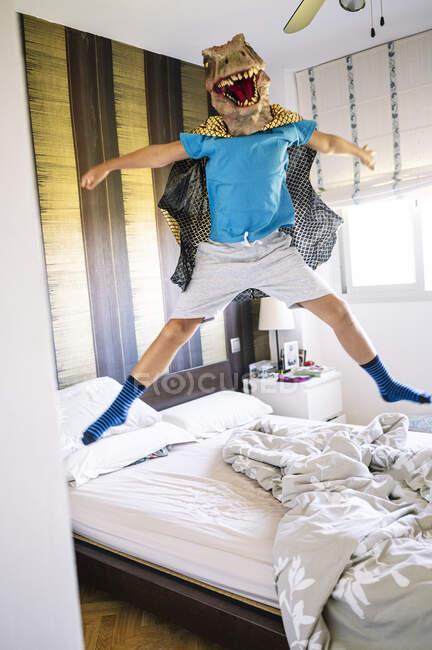 Ragazzo giocoso con maschera di dinosauro e mantello che salta sul letto a casa — Foto stock