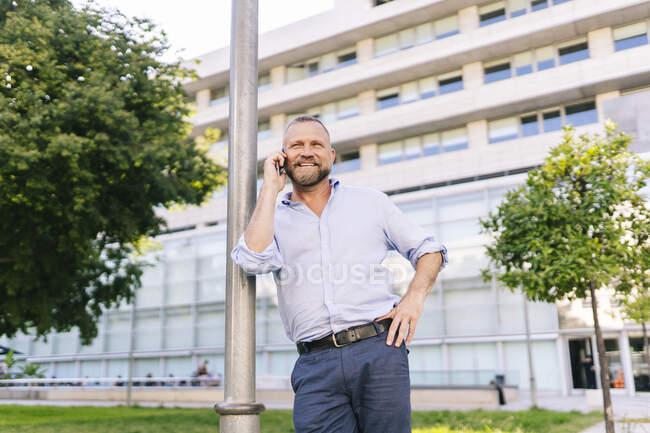 Усміхнений бізнесмен розмовляє по телефону, спираючись на стовп у офісному парку. — стокове фото