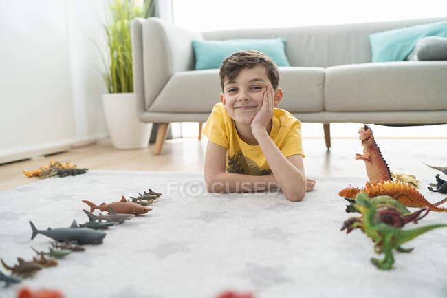 Усмішка з рукою на підборідді лежить іграшкових тварин на килимі у вітальні. — стокове фото