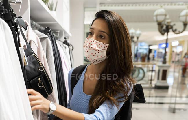 Donna che indossa maschera protettiva mentre guarda i vestiti nel centro commerciale — Foto stock