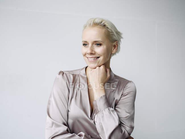 Donna d'affari sorridente con mano sul mento guardando lontano contro il muro bianco in ufficio — Foto stock