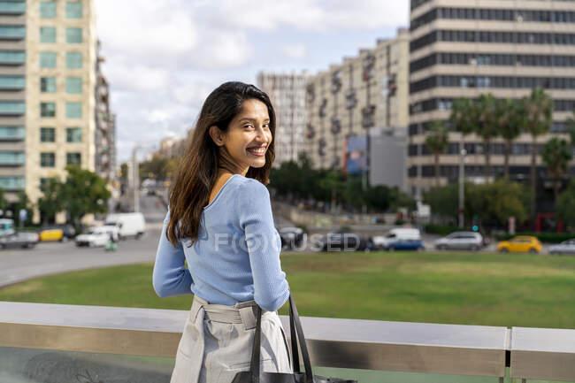 Souriant belle femme d'affaires debout par rambarde tandis que la ville en arrière-plan — Photo de stock
