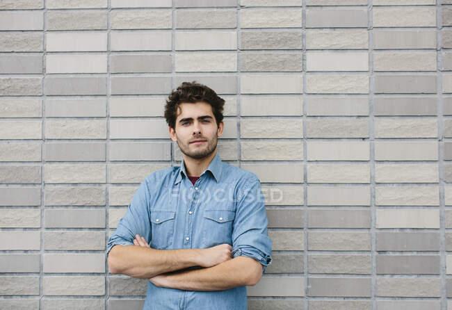 Guapo hombre de negocios casual con los brazos cruzados de pie contra la pared de ladrillo - foto de stock