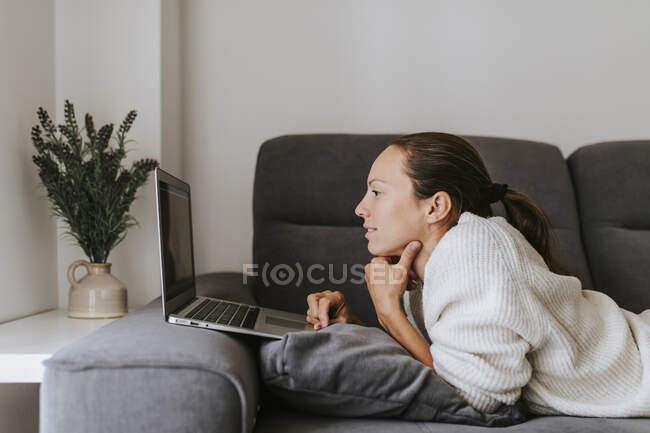 Женщина с ноутбуком, лежащая на диване в гостиной — стоковое фото
