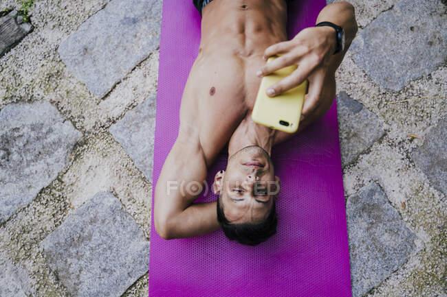 Shirtless male athlete using smart phone while lying on mat — Stock Photo