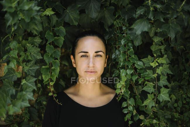 Nahaufnahme einer erwachsenen Frau Mitte 20 gegen Pflanzen im Park — Stockfoto