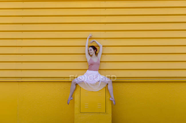 Smiling ballerina with arms raised dancing on seat against yellow wall — стокове фото