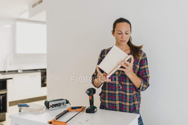 Mid adult woman doing DIY work while standing at home — Stock Photo