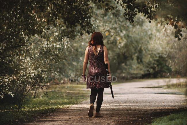 Молода руда жінка, що ходить з кларнетом на стежці лісу. — стокове фото