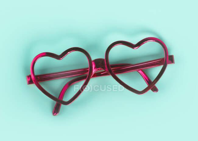 Primer plano de gafas en forma de corazón rosa sobre fondo azul - foto de stock