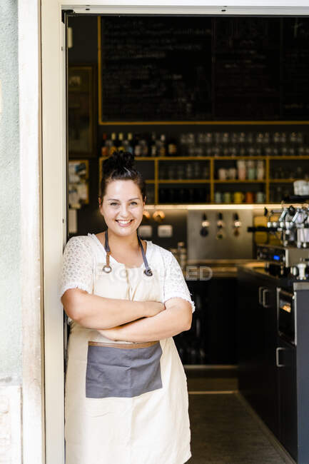 Smiling female owner with arms crossed standing at entrance of cafe — Stock Photo