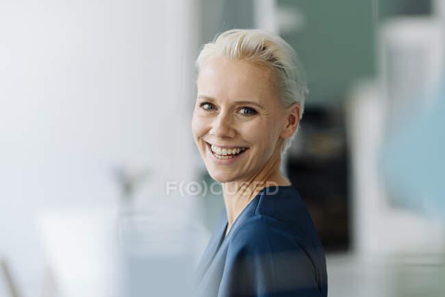 Primer plano de la alegre mujer de negocios con el pelo corto en la oficina - foto de stock