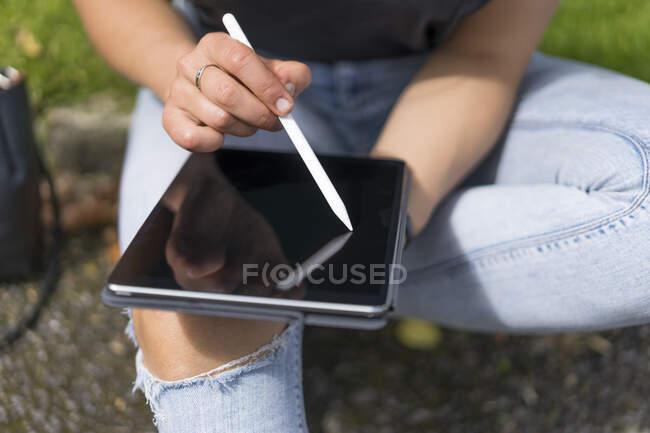 Manos de mujer dibujando en la tableta gráfica mientras está sentado en el parque - foto de stock