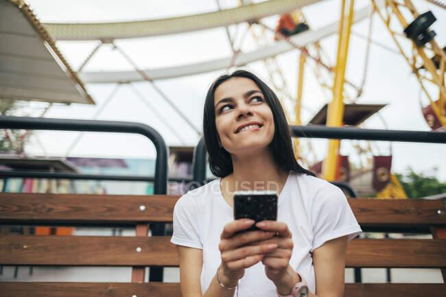 Giovane donna che utilizza smart phone mentre seduto sulla panchina al parco divertimenti — Foto stock