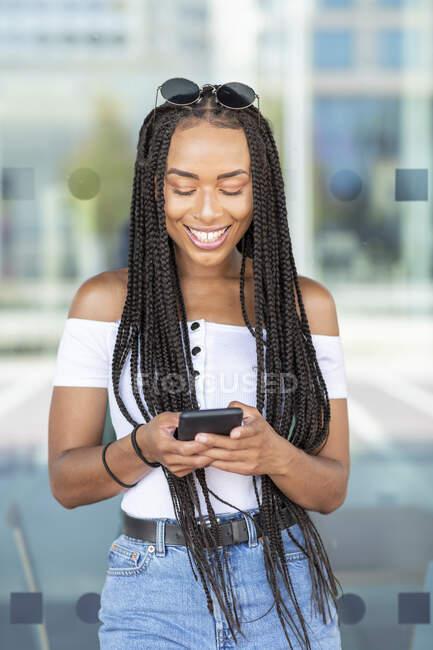 Donna che utilizza il telefono cellulare mentre in piedi contro muro di vetro in città — Foto stock