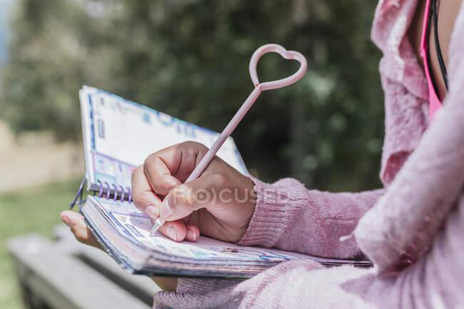 Nahaufnahme einer jungen Frau, die im Park Tagebuch schreibt — Stockfoto