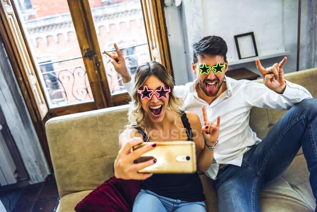 Giocoso giovane coppia indossa occhiali comici e prendere selfie sul divano in soggiorno a casa — Foto stock