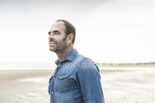 Thoughtful mature man standing at beach against sky during weekend - foto de stock