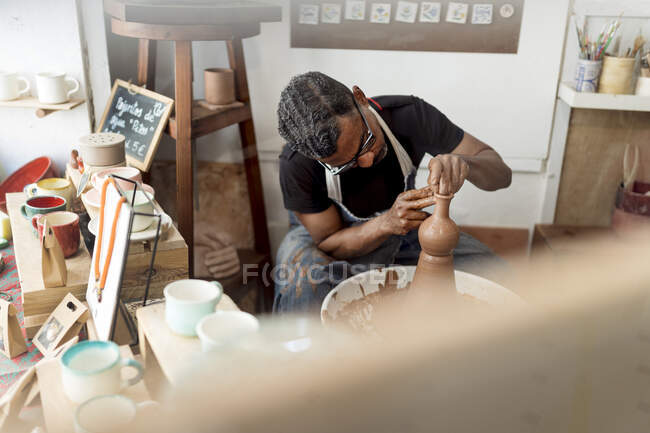 Male potter making earthenware while sitting in workshop — Stock Photo