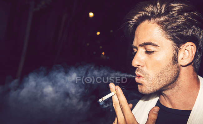 Primer plano del hombre adulto medio fumando cigarrillos al aire libre por la noche - foto de stock