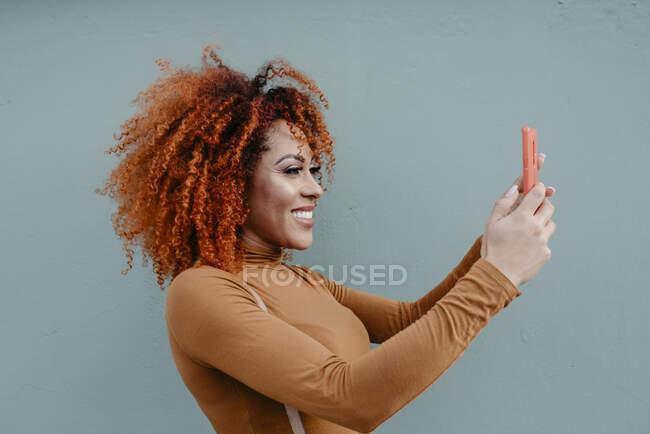 Усміхнена жінка, яка самовіддана, стоячи біля сірої стіни. — стокове фото