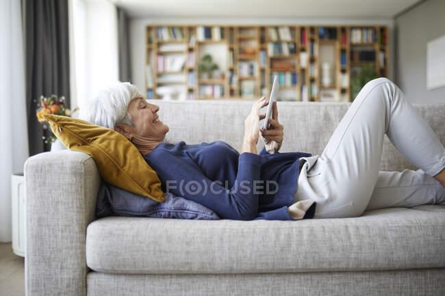 Mensajería de texto de mujer mayor en tableta digital mientras está acostada en el sofá en casa - foto de stock
